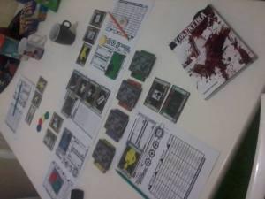 Uma mesa de Violentina: cartas, gabaritos, fichas e até mesmo um tabuleiro - tudo para garantir o máximo de uma sessão.